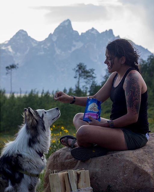 Girl sitting with legs crossed on top of boulder feeding Mountain House Cheesecake bits to white and black dog