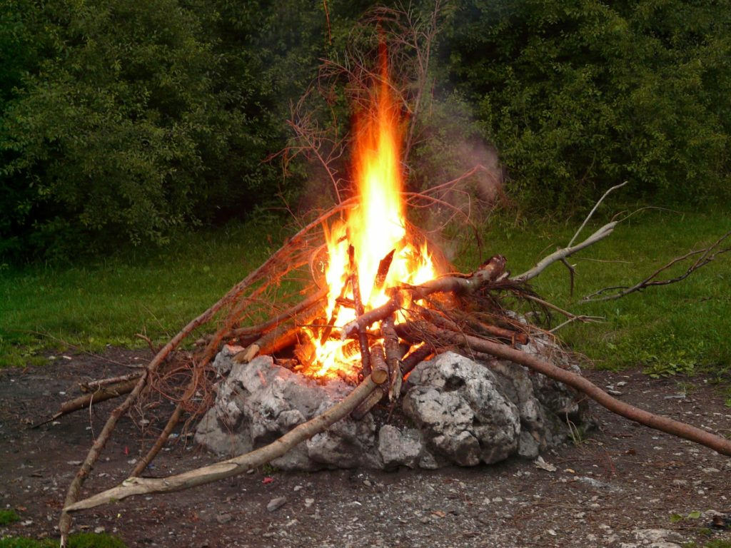 Large campfire in woods.