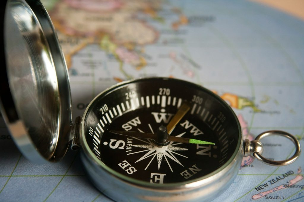 Black magnetic compass on map.