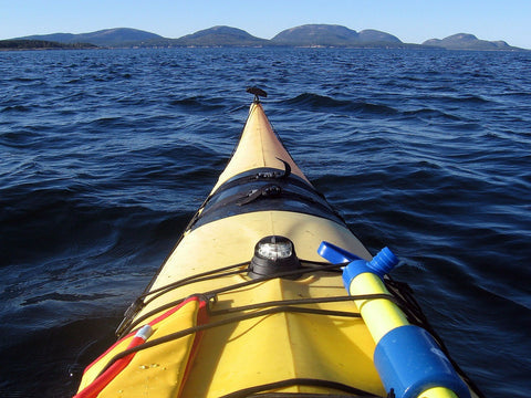 Tip of yellow kayak on Maine river.