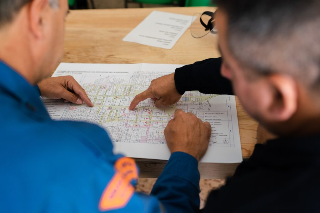 Men study route on map.