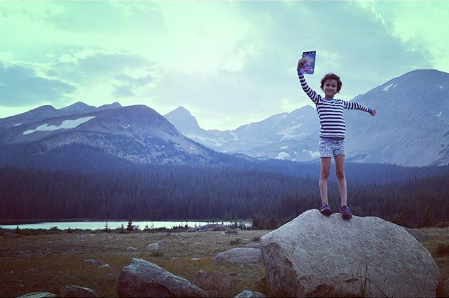 Child standing on rock holding pouch of Mountain House dessert in air with mountains and lake in background