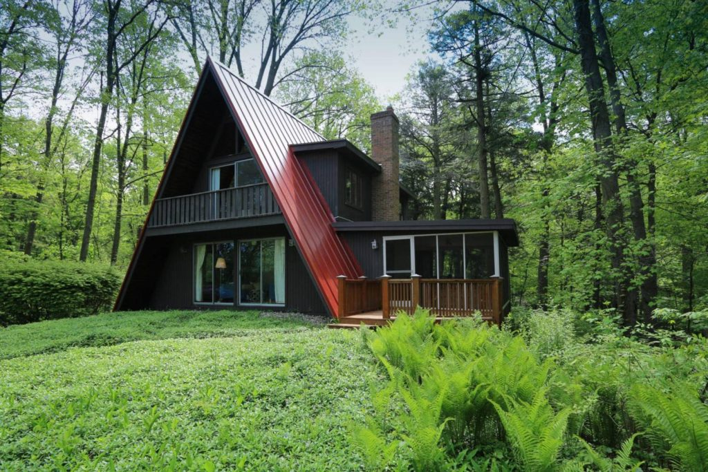 Large A-frame cabin surrounded by green trees and lawn