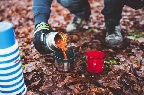Hiker pours soup from thermos into camping mugs.