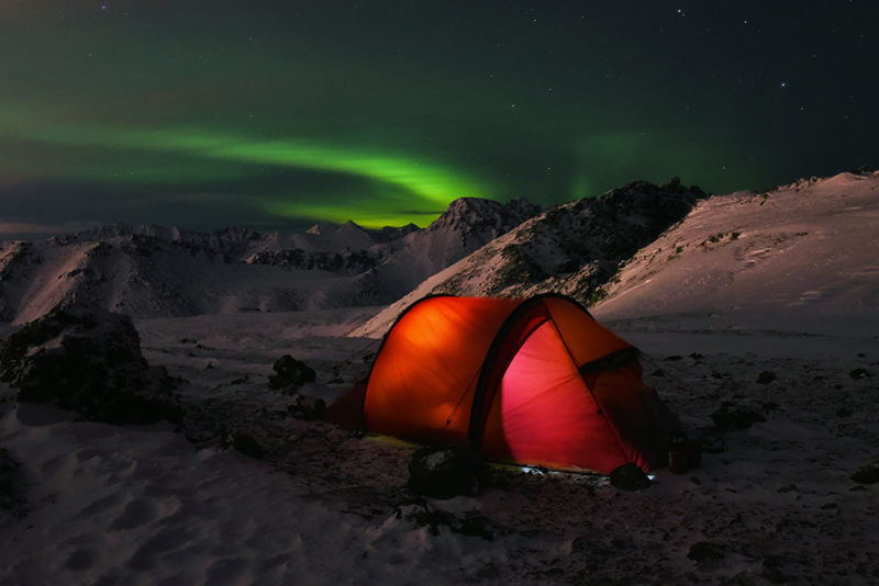 glowing red tent on snow with the aurora in the sky