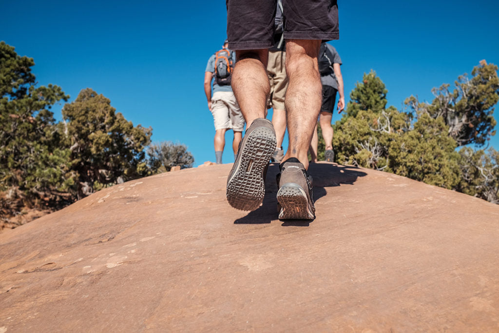 A low angle shot of the back of a hikers calves as they climb up sandstone.
