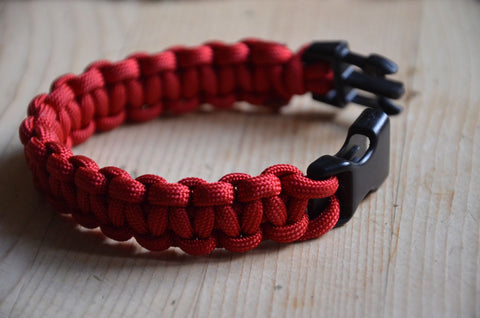 Red paracord bracelet on table.