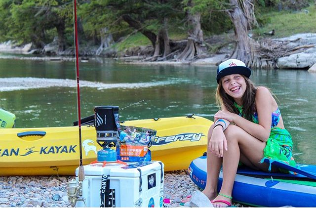 Young girl sitting on a blue blown up kayak next to river laughing. In front of her sits a jetboil on top of cooler next to pouch of Mountain House Beef Stroganoff