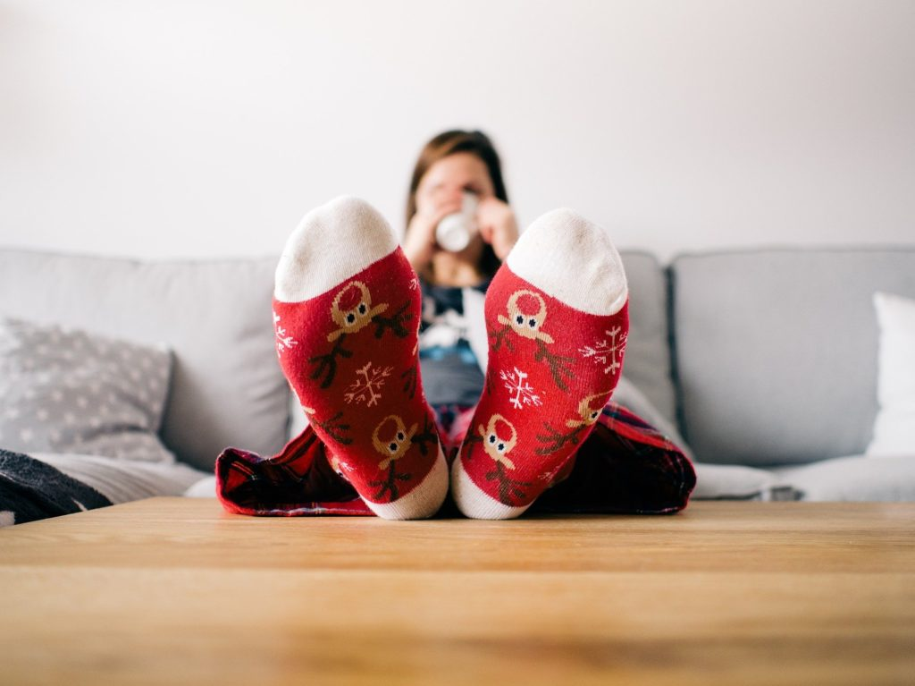 Woman on couch with red fluffy socks propped on table.
