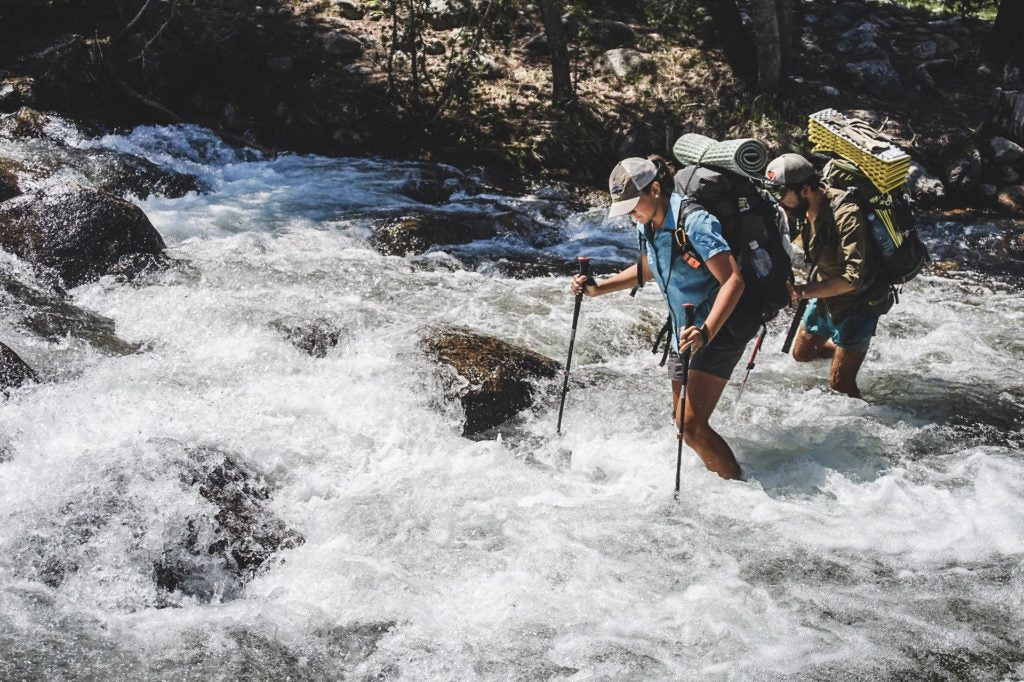 Two backpackers cross a river with their pack belts unfastened and using trekking poles for stability.