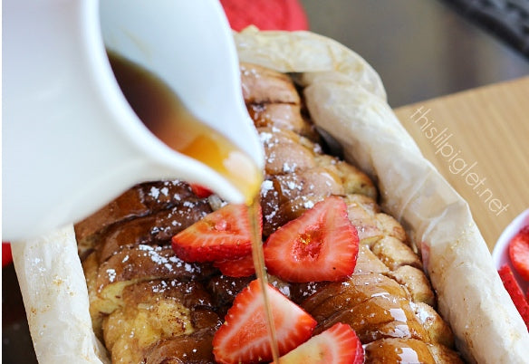 syrup being poured over campfire french toast with sliced strawberries