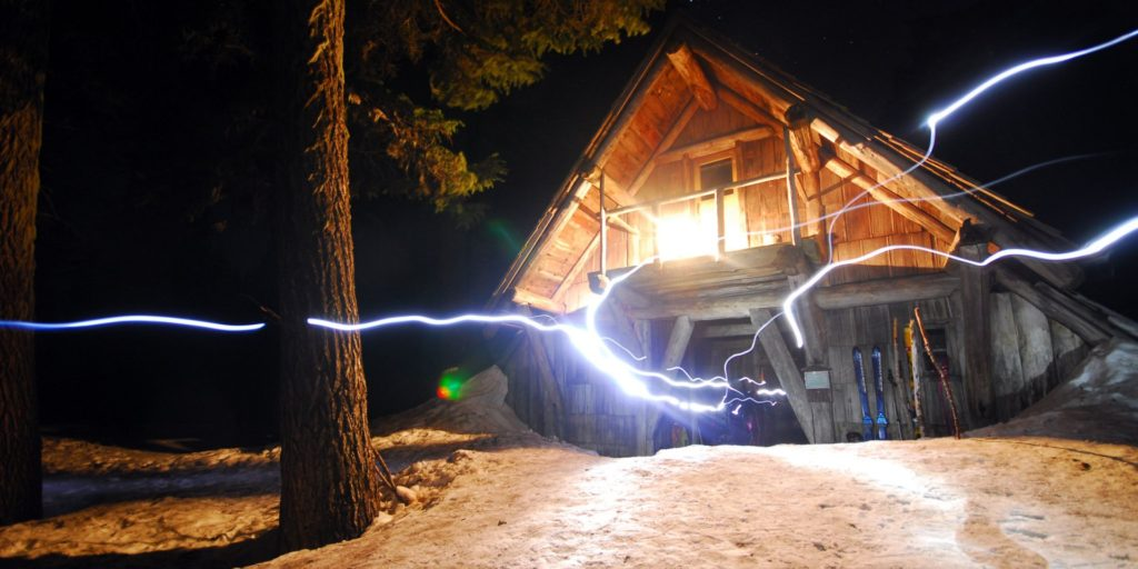 Snowy A-Frame cabin with light painting streaks.