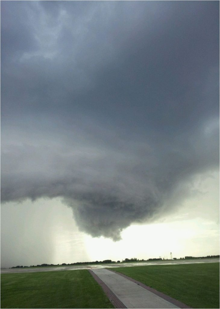 Tornado funnel cloud over road and green fields