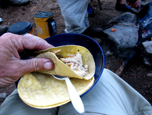 hand holding trout taco at camp