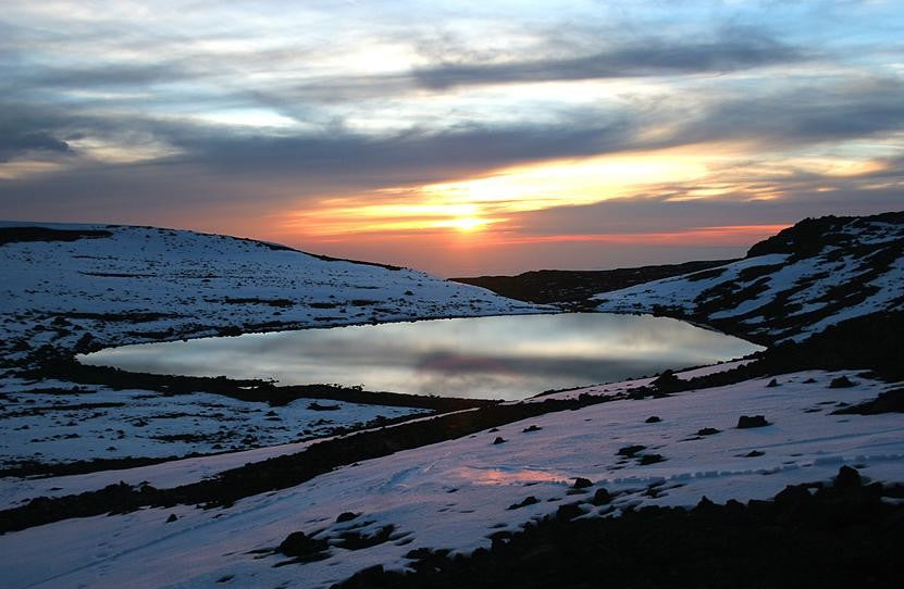 high mountain lake with snow all around at sunset