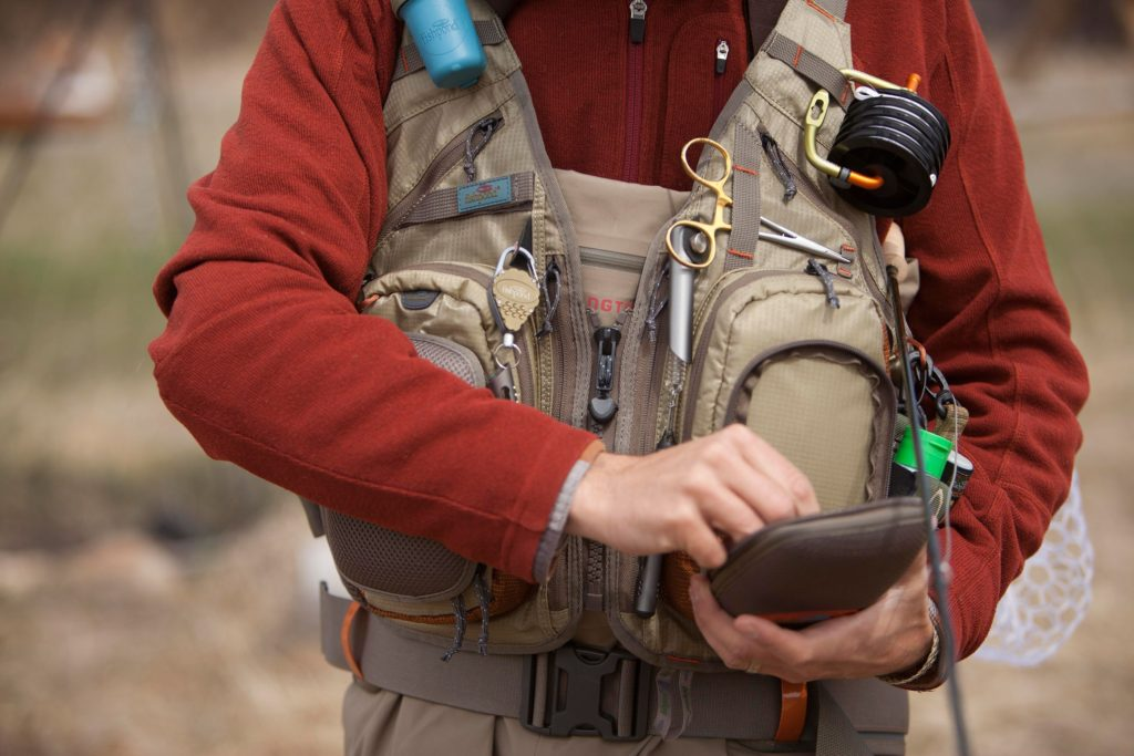 A person in red is wearing a technical fly fishing pack.