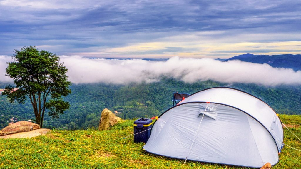 White camping tent set up on grassy mountain peak.