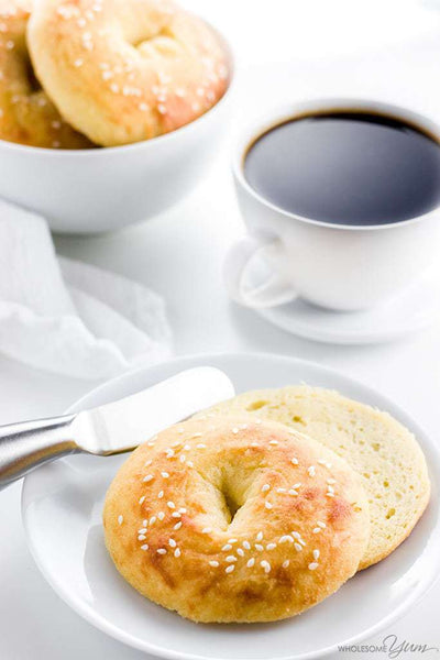 low carb bagels with butter knife on white plate next to cup of dark coffee