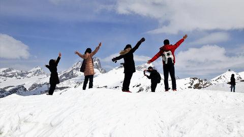 Winter backpackers pose on snowy mountain summit.