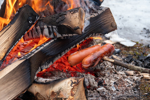Sausages cook on stick by winter campfire.