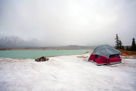 Winter campsite with tent & fire set up by lake.
