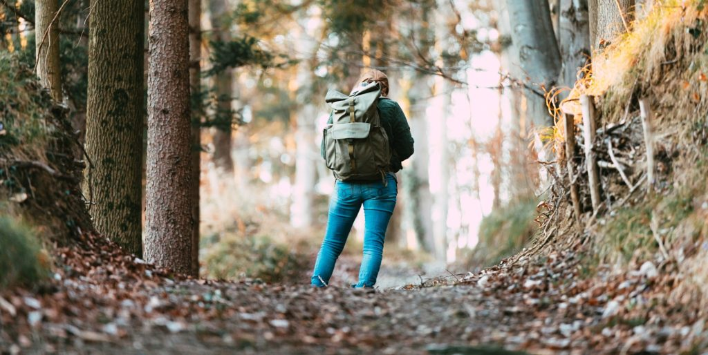 Woman backpacking on forest trail.