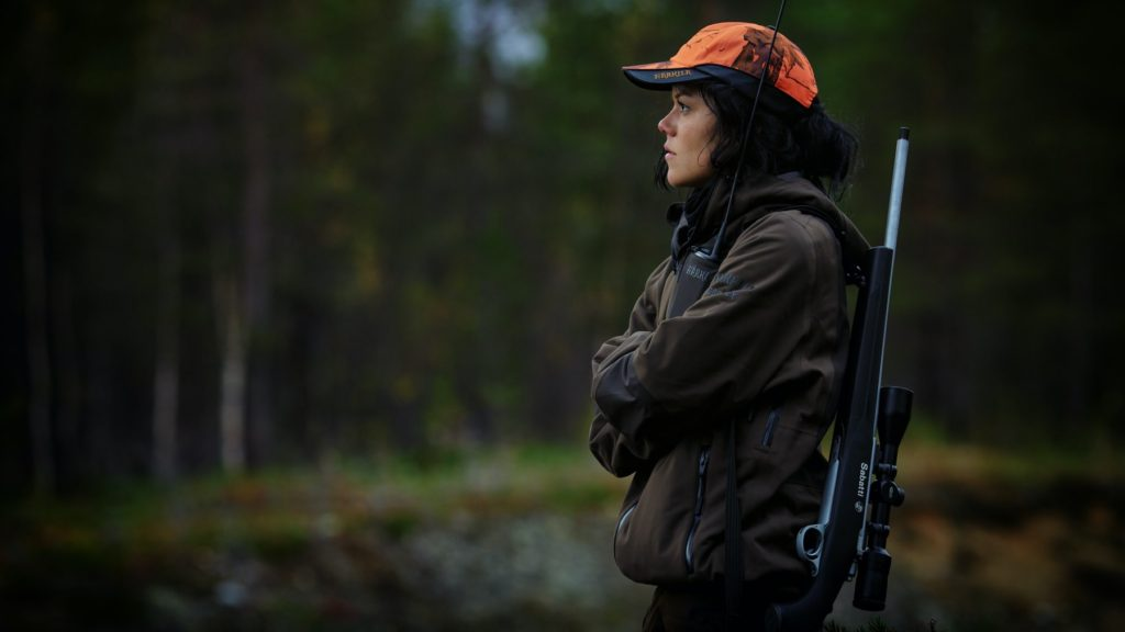 Woman with gun sling and hunter's orange hat standing in forest