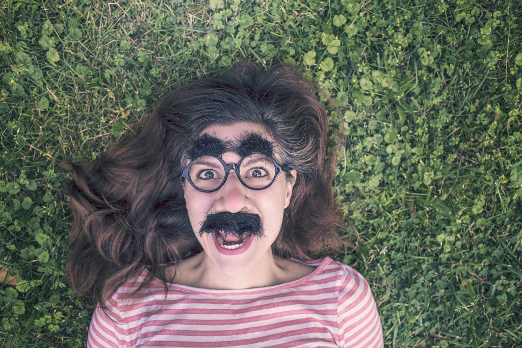Woman with fake mustache, glasses & eyebrows makes funny face on grass.