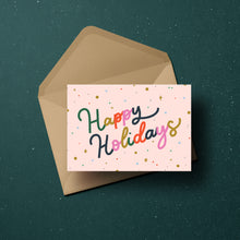 Load image into Gallery viewer, 'Happy Holidays' in colourful lettering surrounded by confetti and merry little stars, set against a blush background.