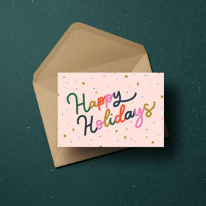 'Happy Holidays' in colourful lettering surrounded by confetti and merry little stars, set against a blush background.