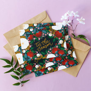 'tis the season' hand lettering surround by a lush illustrations made of NZ flora and holly, all set against a slate blue background.