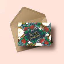 Load image into Gallery viewer, 'tis the season' hand lettering surround by a lush illustrations made of NZ flora and holly, all set against a slate blue background.