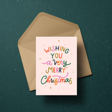 Load image into Gallery viewer, Wishing You a very Merry Christmas in colourful lettering surrounded by merry little stars, set against a blush background