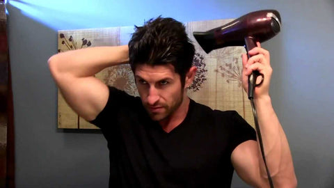 PICTURE OF MAN USING HAIR DRYER
