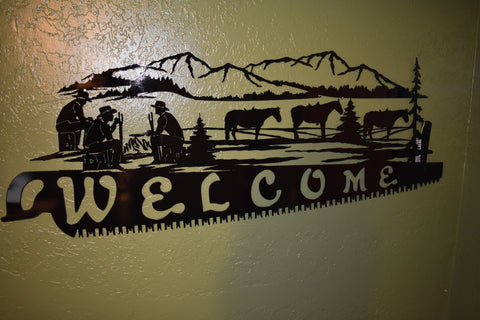Personalized metal wall art of cross cut saw blade with 3 cowboys with horses camping in the mountains