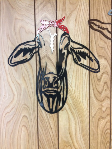 Metal wall art of black brahma cow with a red bow tied on the head.