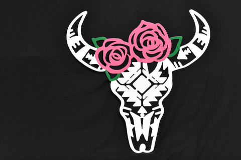 Metal wall art of an Aztec style buffalo skull with colorful Roses on top.