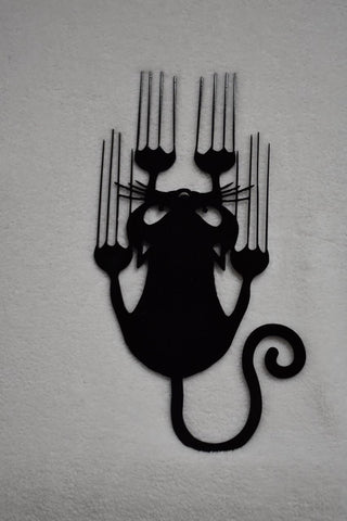 Metal artwork of black Halloween cat sliding down the wall leaving scratch marks