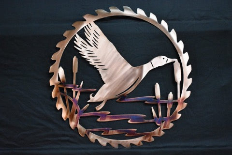 Metal wall art of a copper plated duck flying inside a saw blade.