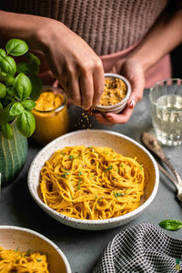 A creamy kabocha squash and red pepper pasta sauce that is made by blending together a mix of vegetables, cashews, spices and broth