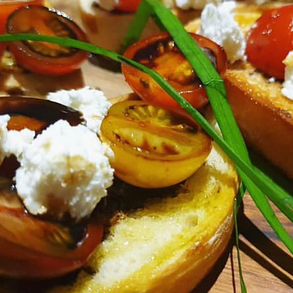 Toasted bruschetta topped with tomato, mozzarella and balsamic