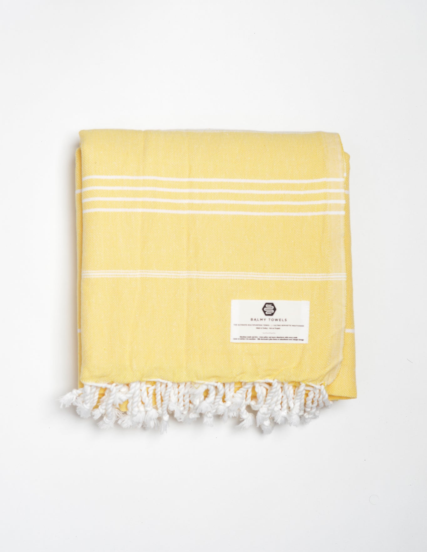 Oversized yellow cotton beach and bath Turkish towel with different sizes of thin white stripes