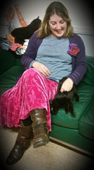 Me petting a cute black kitten who is stretched out on the sofa - Parade Handmade