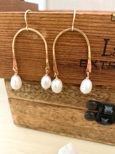 white freshwater pearl drops suspended from a gold fill upside down U shaped frame displayed against a brown box