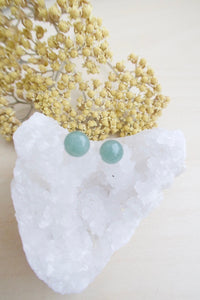 Green aventurine earrings on surgical steel posts sitting on a white crystal