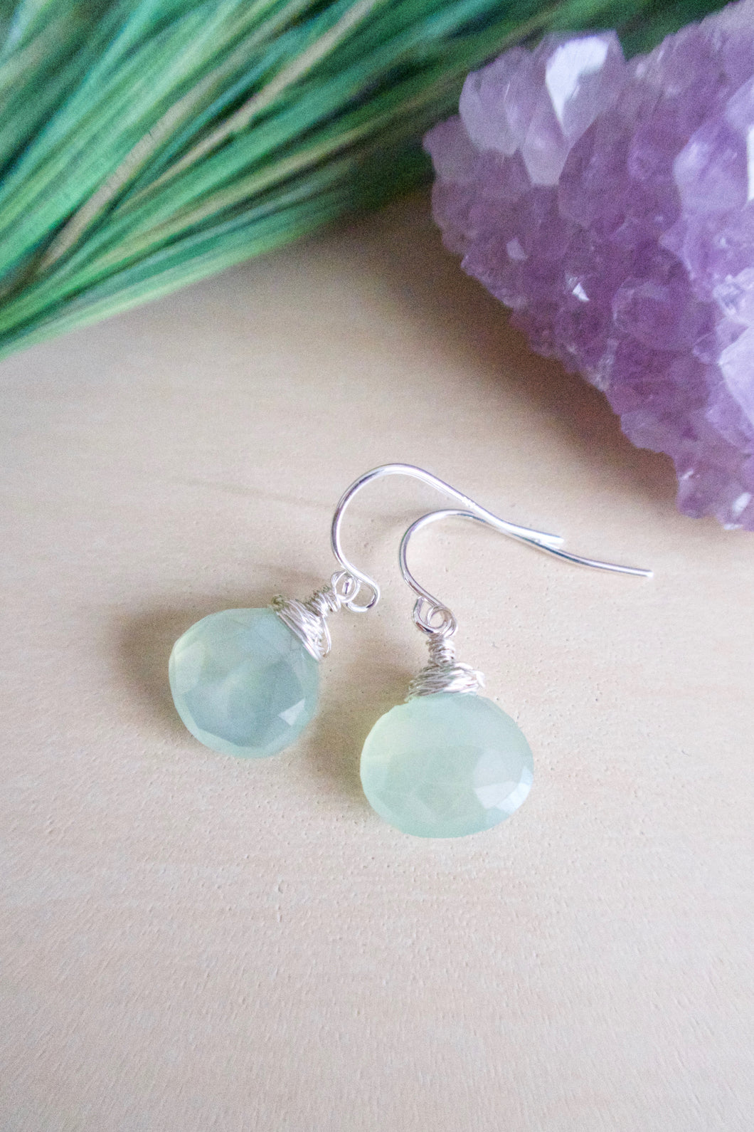 Sea fom green chalcedony gemstone drop earrings wire wrapped in sterling silver wire and suspended from sterling silver ear wires. Pictured on a table