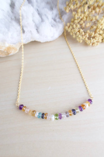 Colorful gemstone bar necklace on a gold chain