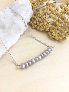 Grey freshwayer pearls arranged in a 1 inch horizontal bar and attached to a rhodium plated chain