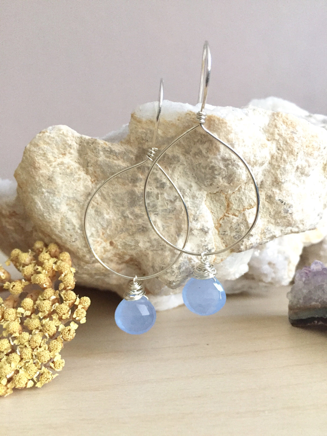 Handmade hoop earrings with a light blue gemstone drop