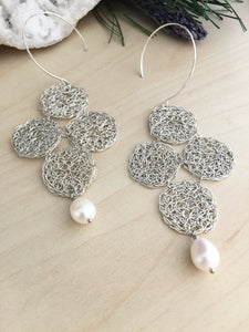Delicate and lacy woven sterling silver earrings in a quaterfoil design and a feshwater pearl drop
